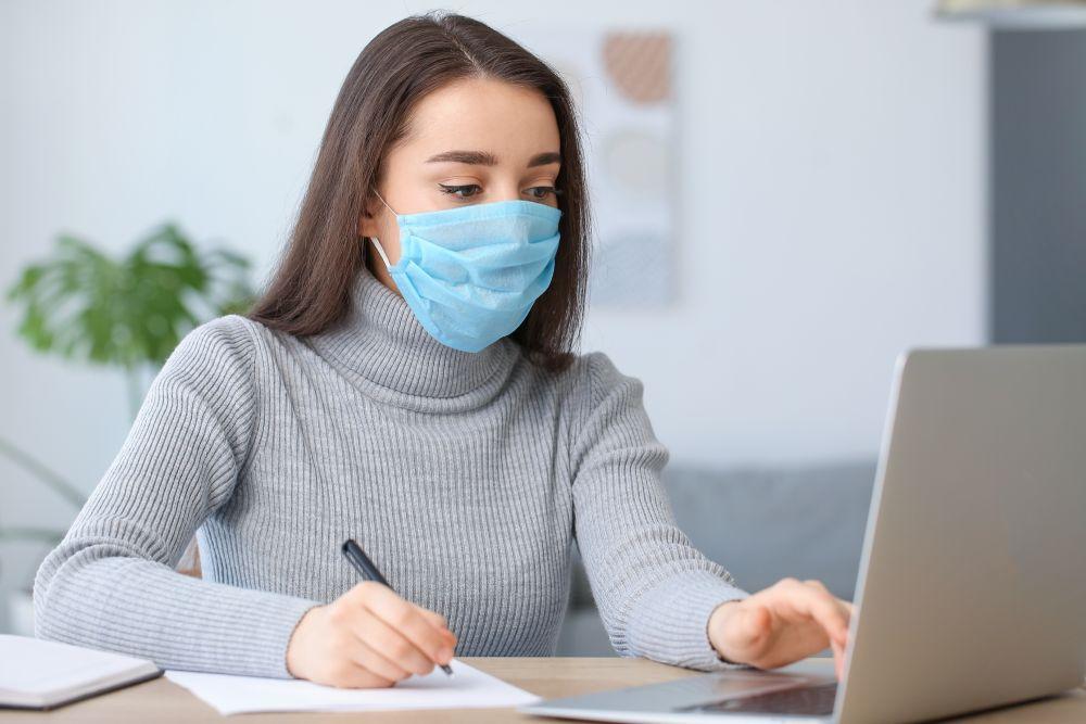 Mladá žena sedící u notebooku s rouškou během koronaviru